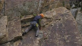 bout : Rock Climbing. Man Puts the Rope in Quickdraw. Slow Motion Stockvideo