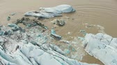melting ice : Svinafellsjokull Glacier Calving. Ice Block Falls in Glacial Lake. Iceland. Aerial View. Stock Footage