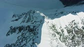 de espaldas : Snowy Top and Ridge of Tall Mountain in European Alps in Sunny Day. Aerial View. Drone Flies Backwards, Tilt Up
