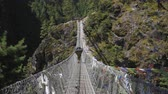 himalaia : Porter is Walking on Suspension Bridge in Khumbu. Himalaya, Nepal. Slow Motion Vídeos