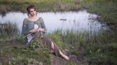 bondade : Fairy tale. The charming girl sitting in the fairy lakeshore. Knitting
