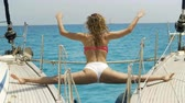 sports : Close-up Shot of a Fit Young Woman Doing Yoga on a Sailing Yacht. In the Background Beautiful Calm Sea and Clear Sunny Sky