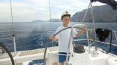 denizci : Litle children captain at the helm controls of a sailing yacht during race. Stok Video