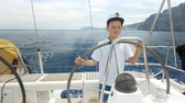 captain : Litle children captain at the helm controls of a sailing yacht during race. Stock Footage