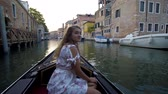 město : Beautiful girl in dress riding on gondola, Venice, Italy.