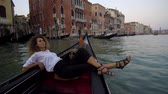 nehrin akıntılı yeri : Girl resting and relaxing in Venice on Gondole ride romance in boat on travel vacation holidays. Sailing in venetian canal in gondola. Italy. Stok Video
