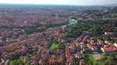 венето : Verona, Italy. Aerial view of famous touristic city Verona in Italy at sunset. Bright sky with illuminated historical buildings and river