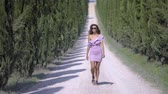 cipreste : Girl in a dress go along the cypress alley, of decorative and neat tall green trees in the park. On a Sunny summer day. 4k