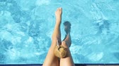 bare : The female legs splashing in pool. Young girl Stock Footage