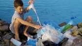 yardım : Litle child volunteer cleaning up the beach at the ocean. Safe ecology concept.