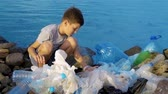 questões : Litle child volunteer cleaning up the beach at the sea. Safe ecology concept.