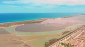 véd : Multicolored salt lakes with coastal salt marshes, aerial view, video shooting with drone. Pink salt lakes and turquoise sea, aerial video.