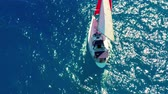 szmaragd : Aerial view. Beautiful sailing yacht with a red sail is sailing on the emerald sea on a sunny day.