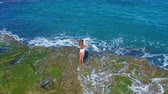 wind : Aerial view. Sexy Girl standing on the Cliff on the Rocky Beach. A woman looks into the distance. Stock Footage