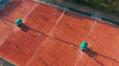 court de tennis : Aerial top view of unrecognizable tennis players playing tennis on the orange court on a sunny summer day. Vidéos Libres De Droits