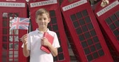 cabine telephonique : Slow motion portrait of cute boy waving British flag standing outdoors alone smiling looking at camera. On the background English red telephone booths. Travelling concept.