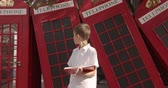 cabine telephonique : Slow motion portrait of cute boy standing outdoors alone smiling looking at camera. On the background English red telephone booths. Travelling concept. Vidéos Libres De Droits