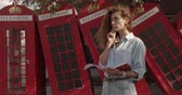cabine telephonique : Attractive girl walking on a background of red British phones. Travel, tourist places concept.