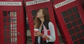 cabine telephonique : Attractive girl walking on a background of red British phones. Drinks coffee and sightseeing. Vidéos Libres De Droits
