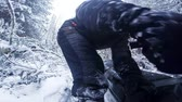 Frustrated Man Having Difficulty to Start his Snowmobile Engine in Forest