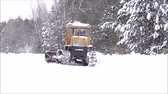 híbrido : Clearing snow from the road. Crawler Tractor grader clears snow from the road. The snow is fresh, it has dropped recently. Snow White, fluffy and beautiful. Road service road from the clean fresh snow. Around the beautiful snow-covered forest.