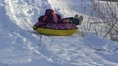 rury : SLOW MOTION: Girl child rolls on a toboggan running on a sled tubing. The child likes to downhill slope in the winter. Winter sunny frosty day. Wideo