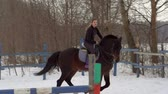 ипподром : SLOW MOTION: A girl jockey fulfills riding on a horse. It performs a variety of sports movement and jumping. Training takes place in a small special paddock. A cloudy winter day. Стоковые видеозаписи