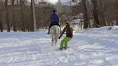 cval : SLOW MOTION: A girl galloping on a horse at a gallop. A horse is dragging a snowboarder guy on a rope. A snowboarder rides on a snowboard in snowdrifts. Girl jockey and guy snowboarder train in pairs. A sunny winter day.
