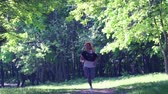 spor ayakkabısı : SLOW MOTION: Girl runs through the park in the morning. Morning invigorating charging.