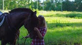 уздечка : Young blonde woman takes a walk with his horse. A woman is training a horse. Summer sunny evening.