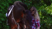 dressage : Young blonde woman takes a walk with his horse. A woman caring for a horse. Summer sunny evening. Stock Footage