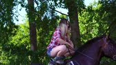 dressage : Young blonde woman takes a walk with his horse. A woman stands on a horse. Summer sunny evening. Stock Footage