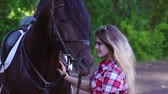ás : Young blonde woman takes a walk with his horse. A woman caring for a horse. Summer sunny evening. Stock Footage