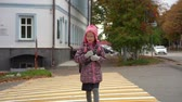 torebki : Girl child the schoolgirl goes home after school. The girl crosses the road at the pedestrian crossing. Slow motion.