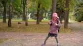 spacer : After studying at school. Girl child schoolgirl Minute rest in the park after school. Slow motion. Wideo