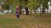 школьница : After studying at school. Girl child schoolgirl collects autumn maple leaves in the park. Maple leaves are needed for girls crafts. Slow motion.