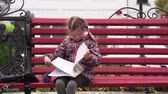 paper bag : Girl child with glasses A girl sits on a park bench. Autumn day.