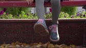 bank : Girl child sits on a bench and her legs. Close-up of childs feet. Autumn day.