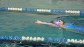 yüzücü : SLOW MOTION: Female athlete swimming on her back. Splashes of water scatter in different directions. Stok Video