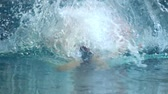 yüzücü : SLOW MOTION: Female athlete swims with a butterfly style. Splashes of water scatter in different directions. Stok Video