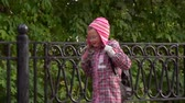 pigtails : Girl child walks along the path along a beautiful iron fence. A girl walks in the park after school. Autumn day.