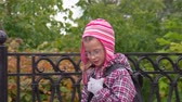engomar : Girl child walks along the path along a beautiful iron fence. A girl walks in the park after school. Autumn day.