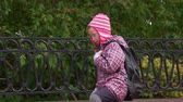 zöpfe : Girl child walks along the path along a beautiful iron fence. A girl walks in the park after school. Autumn day.
