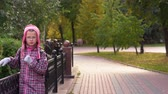 bag : Girl child walks along the path along a beautiful iron fence. A girl walks in the park after school. Autumn day.