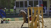 eyer : SLOW MOTION: A young woman jockey on a small horse (pony) performs at equestrian competitions. Summer sunny day.