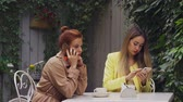 average age : A middle-aged red-haired woman in a brown coat and a brown-haired young woman in a yellow coat are sitting in a summer street cafe and talking on the phone. Close-up.