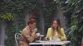 average age : A middle-aged red-haired woman in a brown coat and a brown-haired young woman in a yellow coat are sitting in a summer street cafe and eating dessert. Close-up.