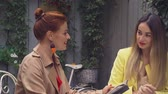 average age : A middle-aged red-haired woman in a brown coat and a brown-haired young woman in a yellow coat are sitting in a summer street cafe and choosing what to order. Close-up. Stock Footage