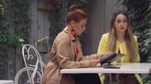 average age : A middle-aged red-haired woman in a brown coat and a brown-haired young woman in a yellow coat are sitting in a summer street cafe, chatting and choosing what to order. Close-up.