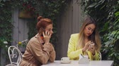 average age : A middle-aged red-haired woman in a brown coat and a brown-haired young woman in a yellow coat are sitting in a summer street cafe and communicate by phone. Close-up. Stock Footage